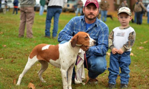 John Bates of Glade Hill poses for a photo with his son Hunter and his hound before the hound bench show on Saturday. Thousands attended the Blue Ridge Folklife Festival at Ferrum College on Saturday, Oct. 27, 2012. (photo by Pat Jarrett)